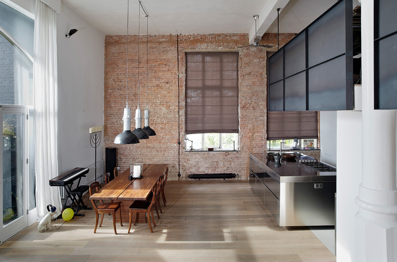 Open plan living space with exposed red brickwork and large industrial windows