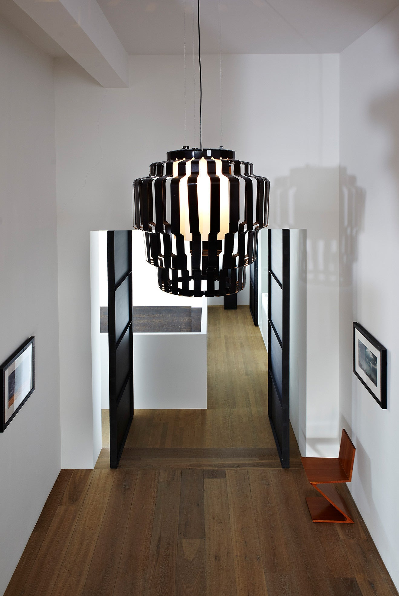 Large black industrial pendant light on the landing hallway section