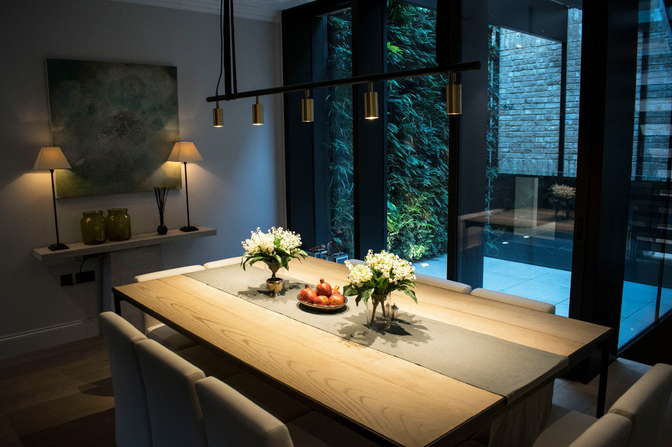wooden dining table with brass feature lighting Echlin Kenure House Holland Park