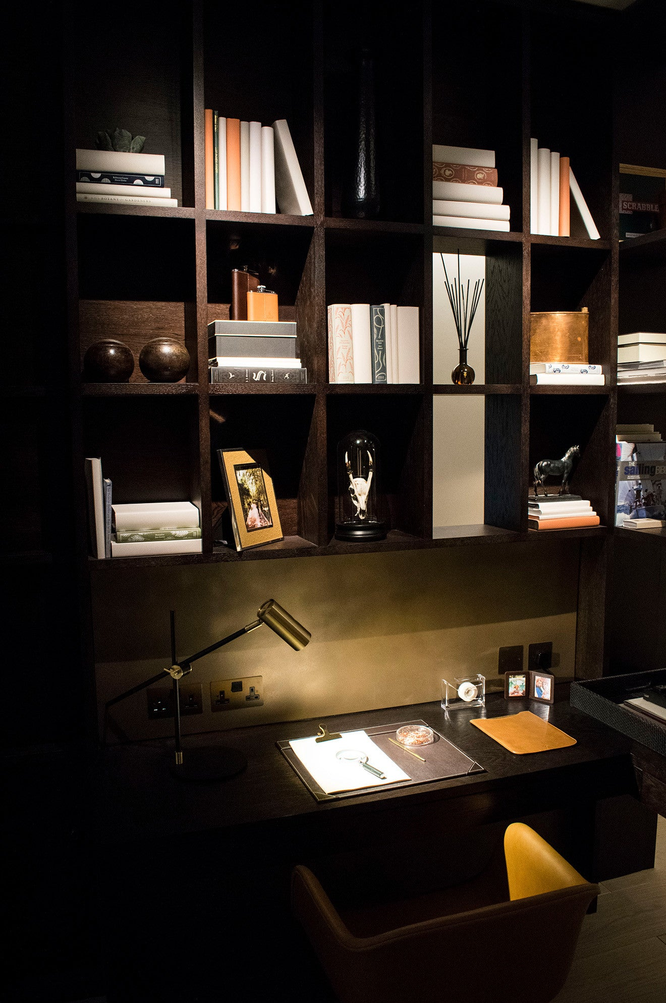 Luxury basement study with dark wood shelving and brass accessories