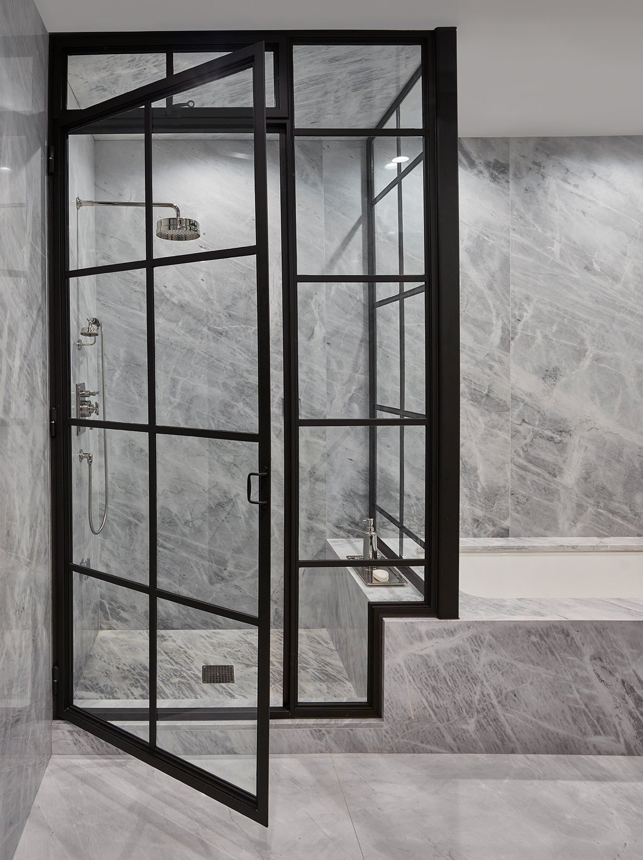 Grey marble bathroom with black industrial and glass shower cubicle