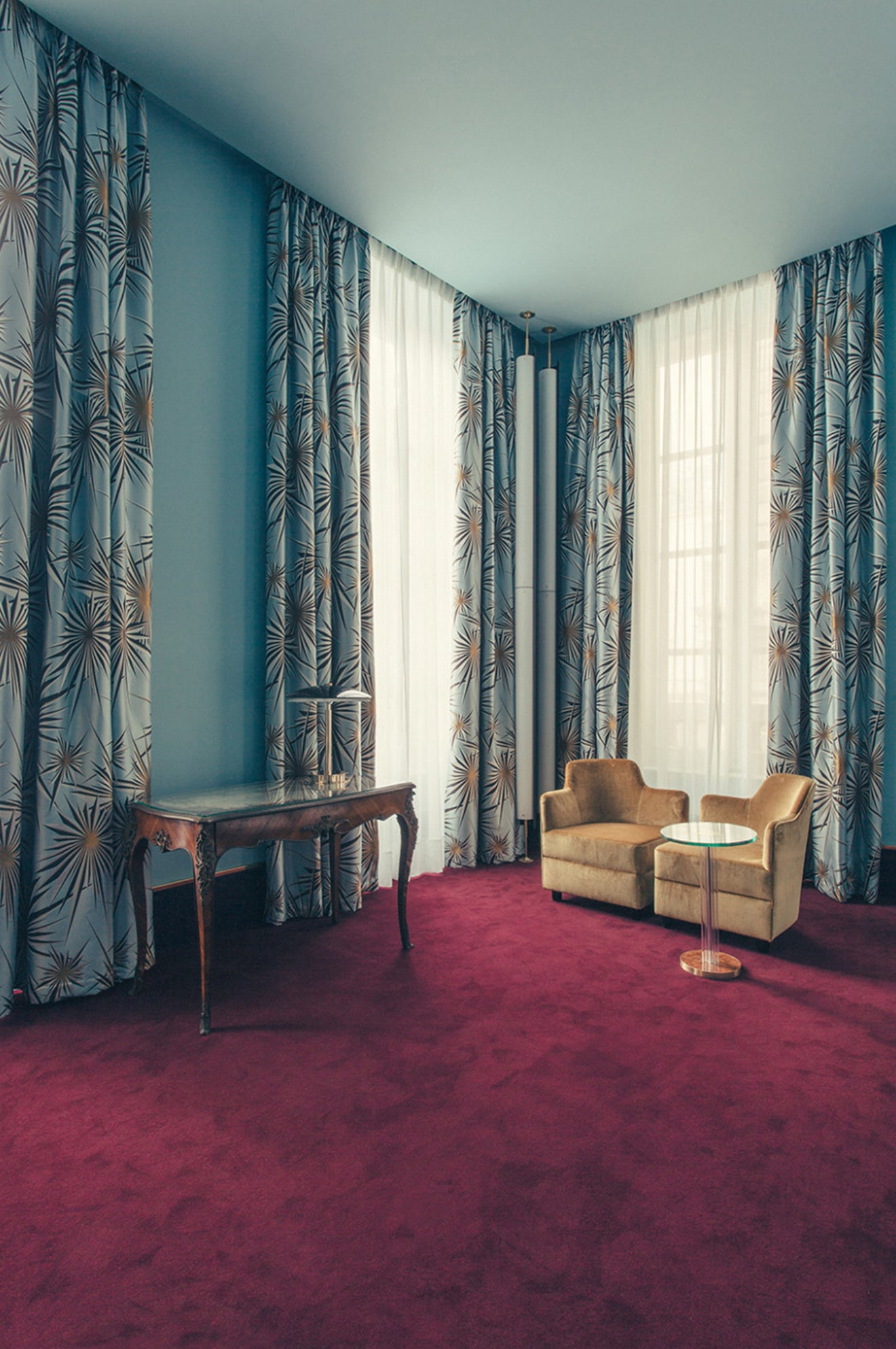 pastel blue retro hotel suite with red carpet