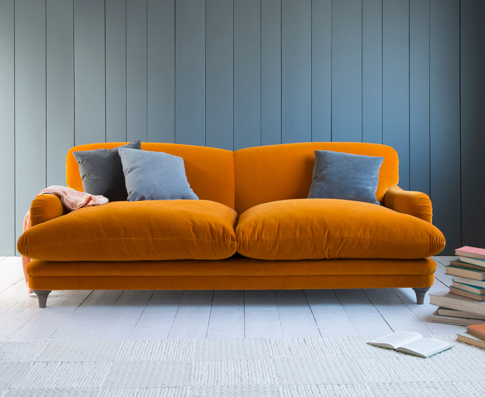 Loaf burnt orange pudding sofa with blue combination cushions