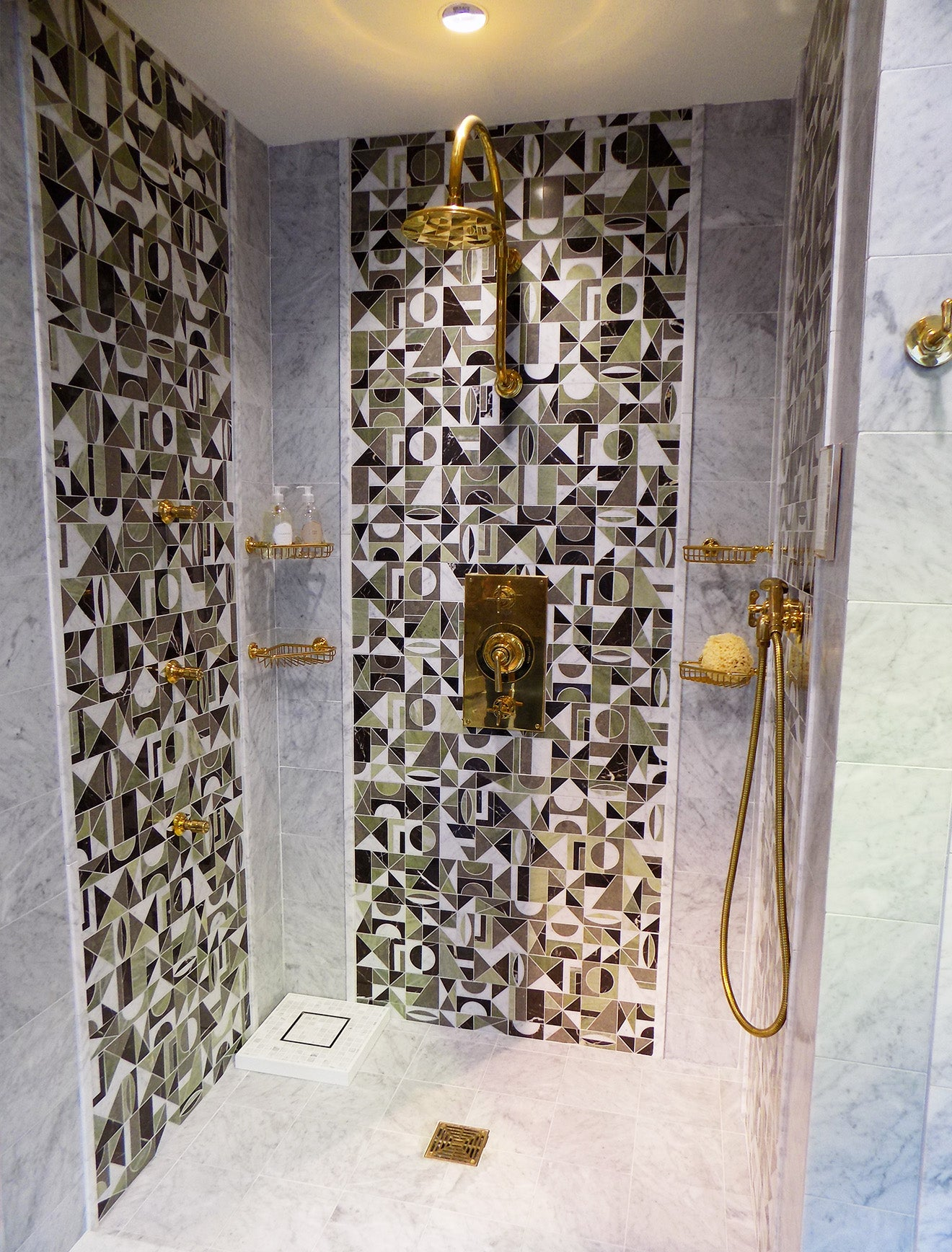 Modern brass shower cubicle with green abstract tiles