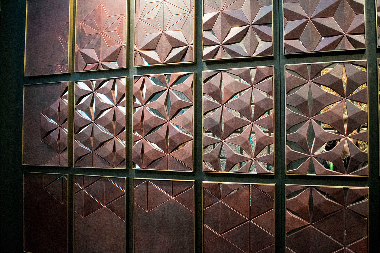 deep red brown leather wall covering geometric design with mirror backing and brass framing