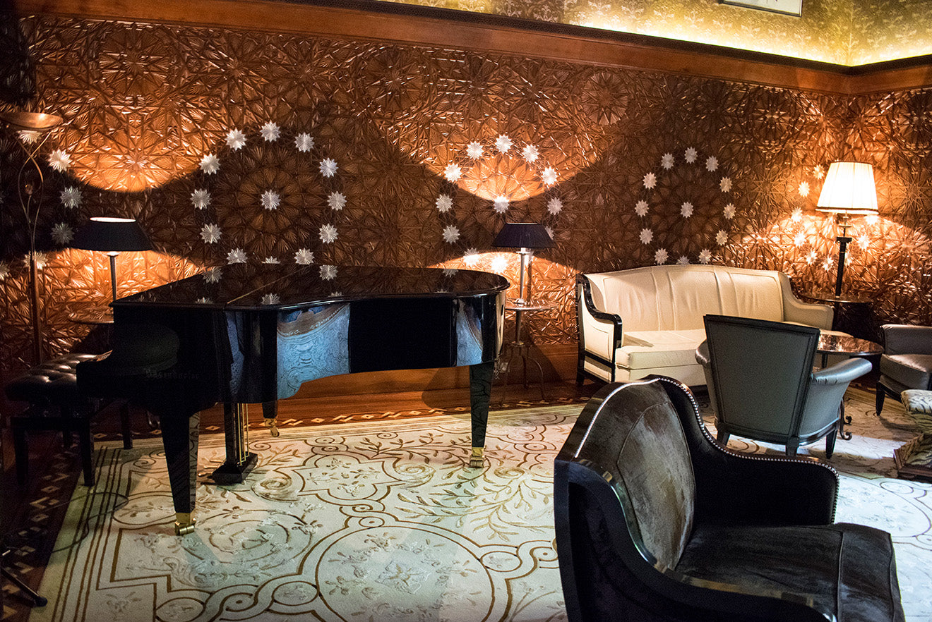 Black grand piano against the luxury Moroccan style paneling