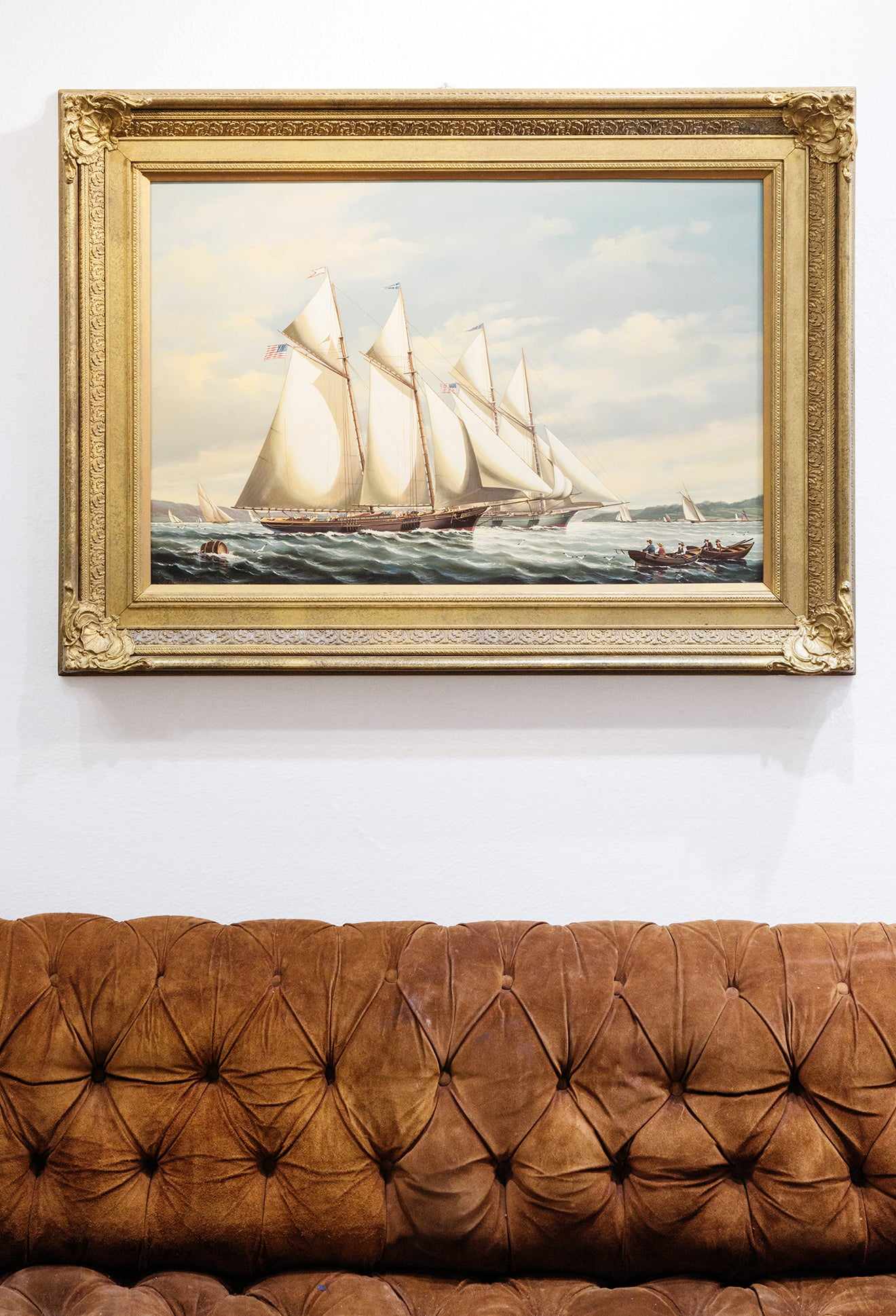 Sailing painting with gold frame next to tanned chesterfield sofa