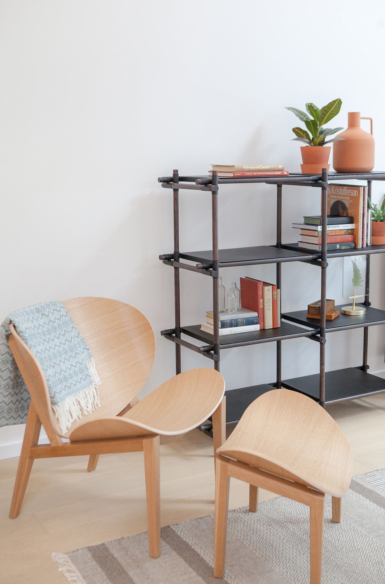 Scandinavian arm chair with stool and scaffolding shelving unit