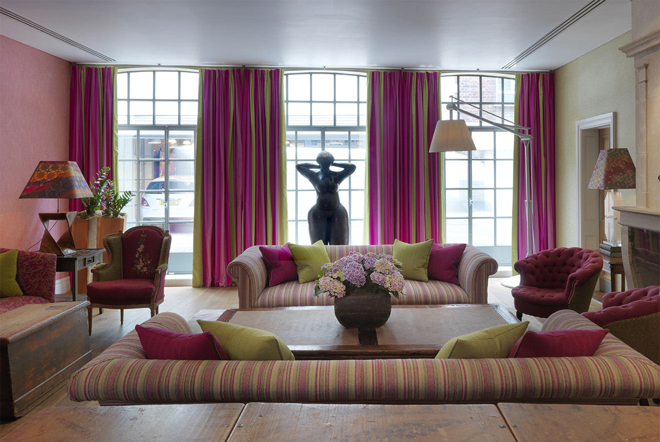 Soho Hotel library room with bright pink curtains and striped sofa