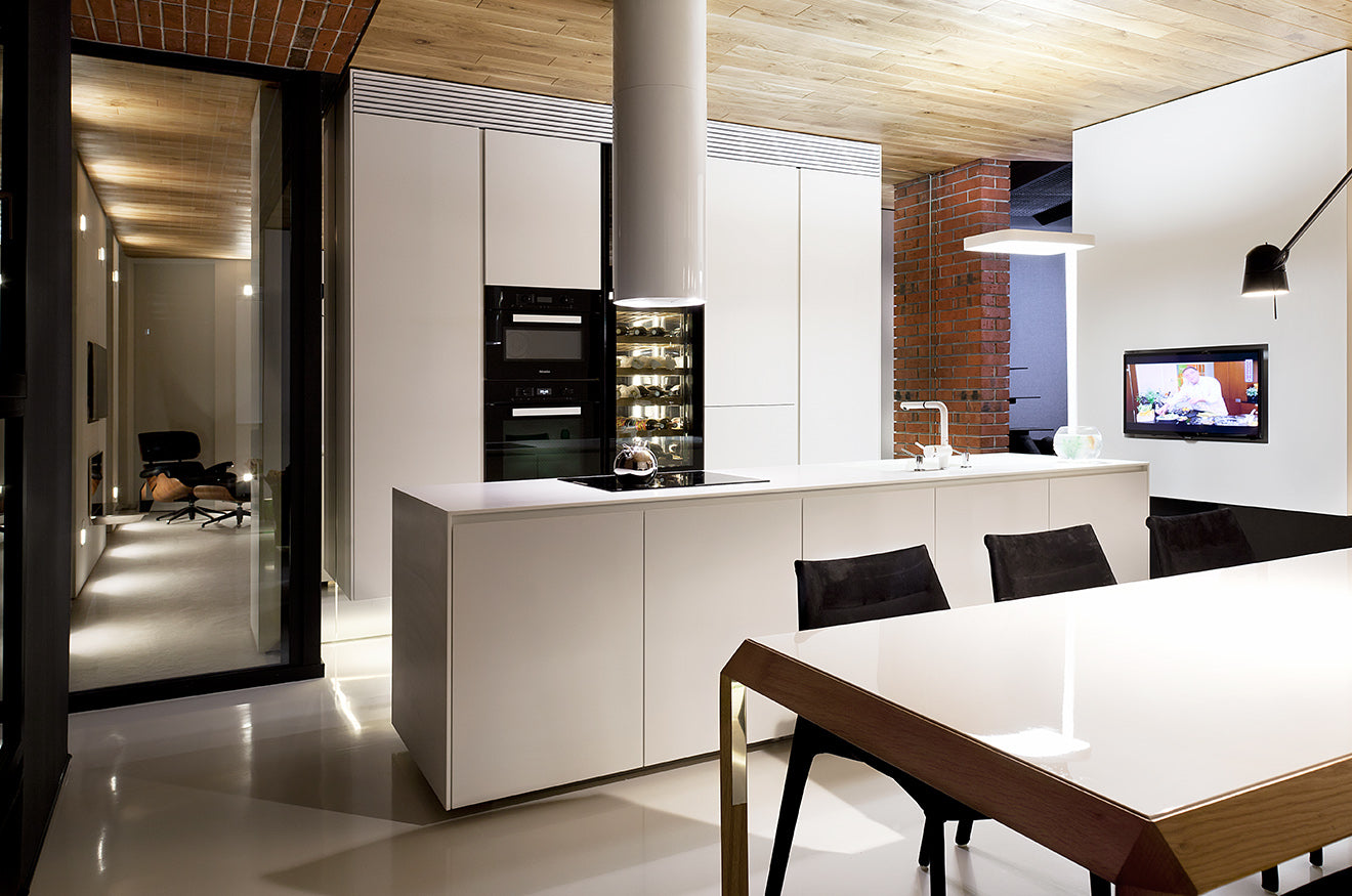 Modern industrial style kitchen with white lacquered finish, red brick and natural wood