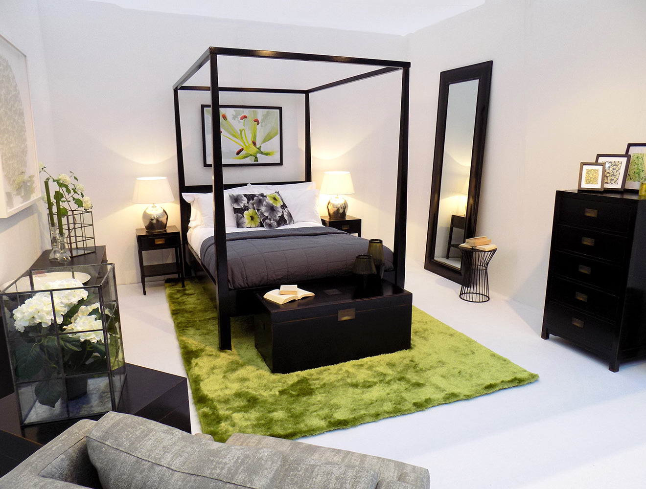 Minimalist summer bedroom with green rug, black furniture and white walls
