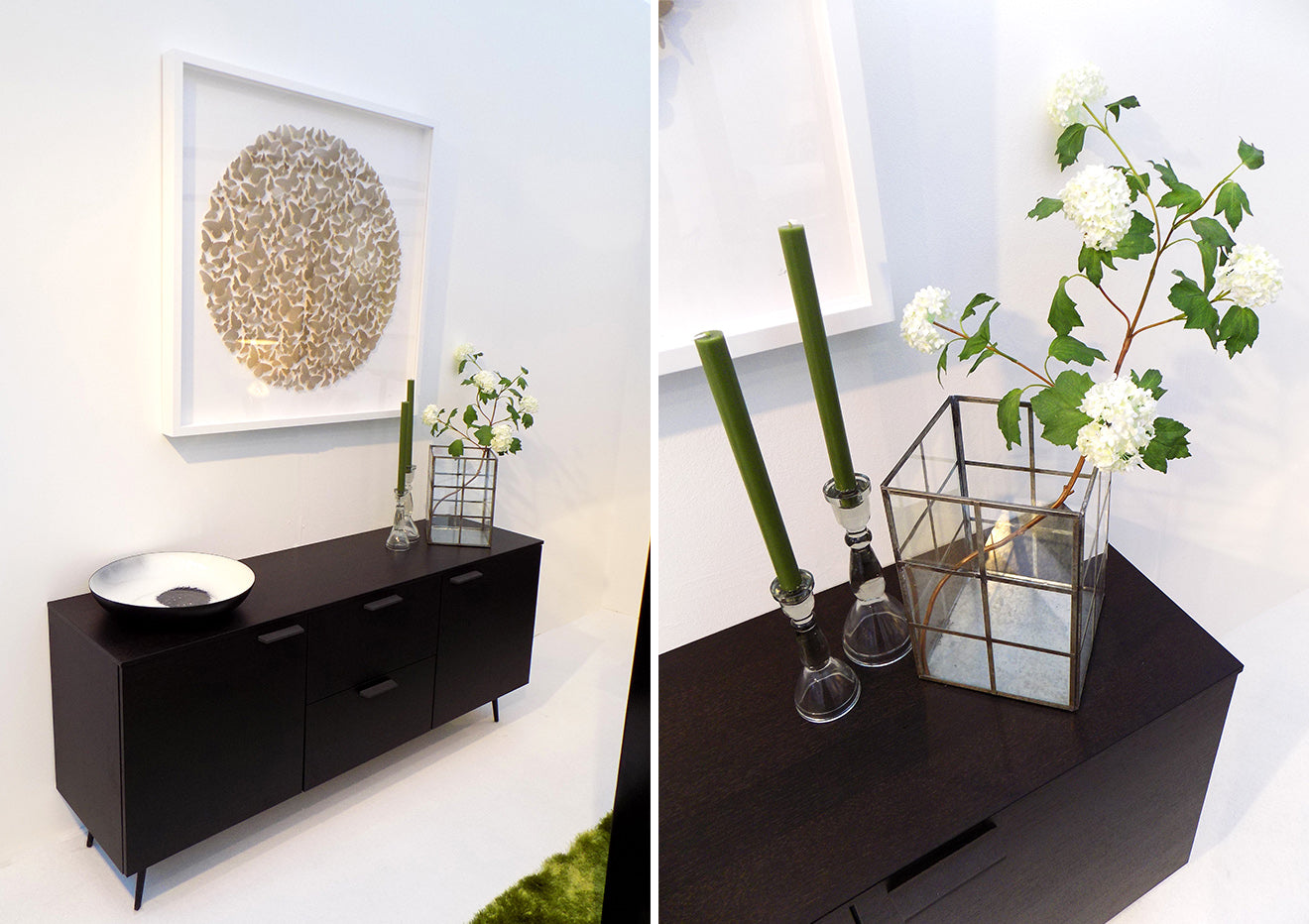Black sideboard with glass cube vase, flowers and butterfly artwork