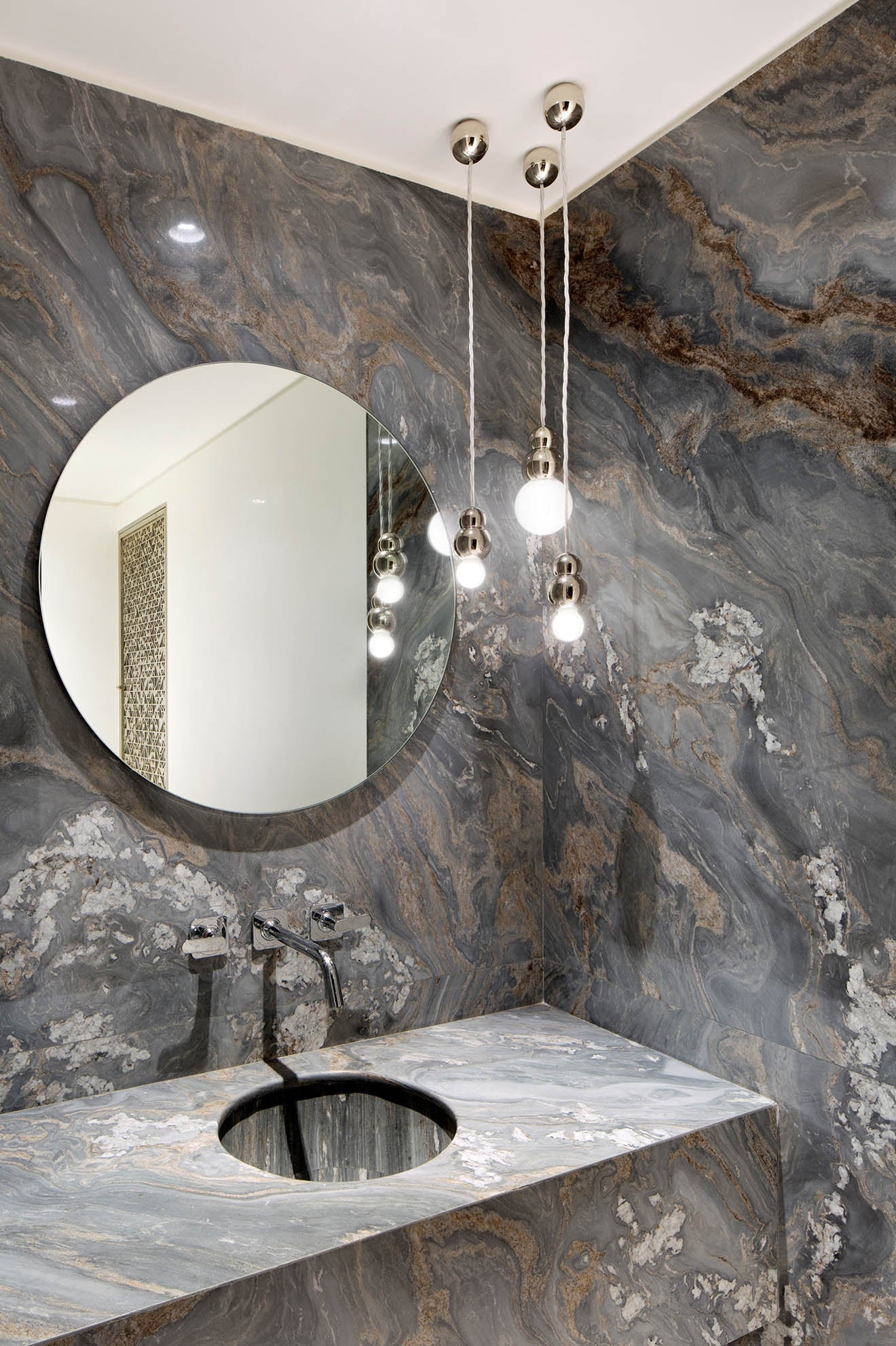 Luxury modern marble washroom with circular mirror and pendant lighting