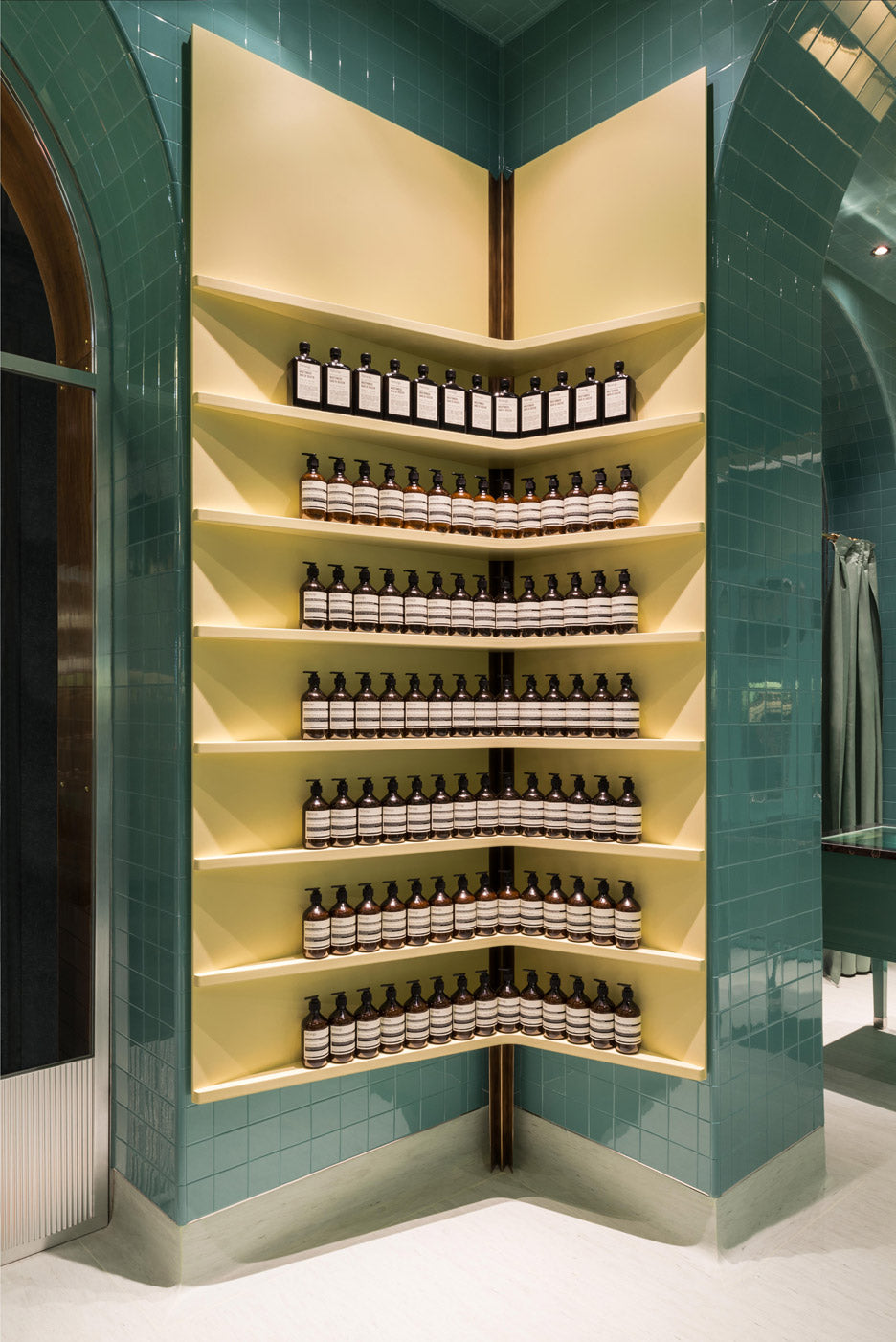 Aesop display in their Milan store yellow against green tiles