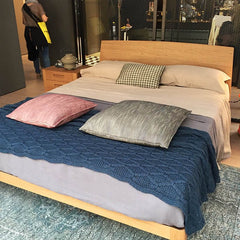Bed on display at 100% Design London with blue thick cable knit throw