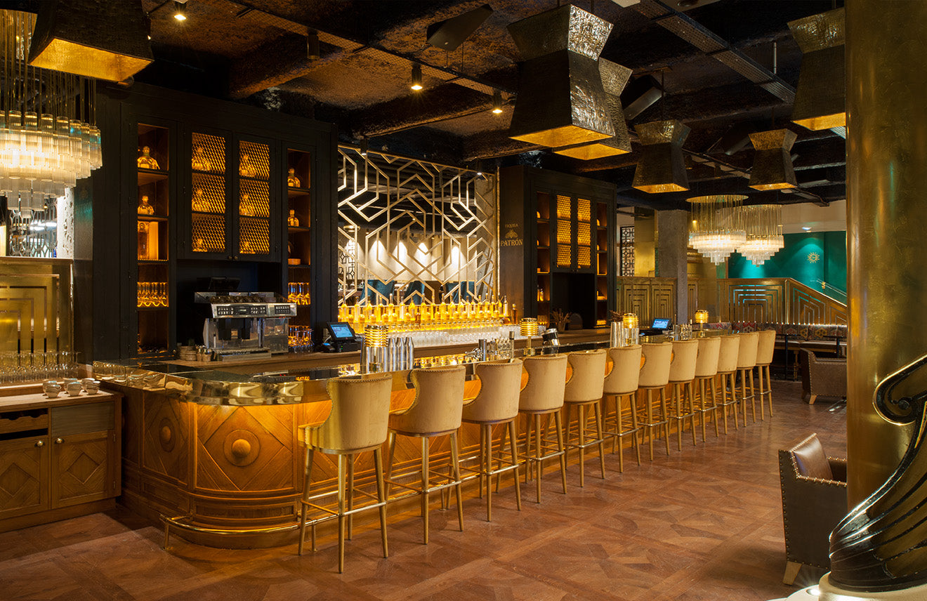 Luxury gold restaurant with cream bar stools and extravagant lighting