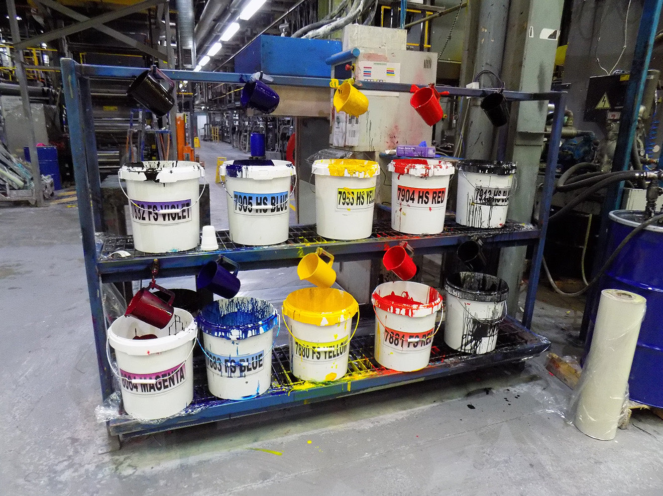 brightly coloured paint in tubs at the factory