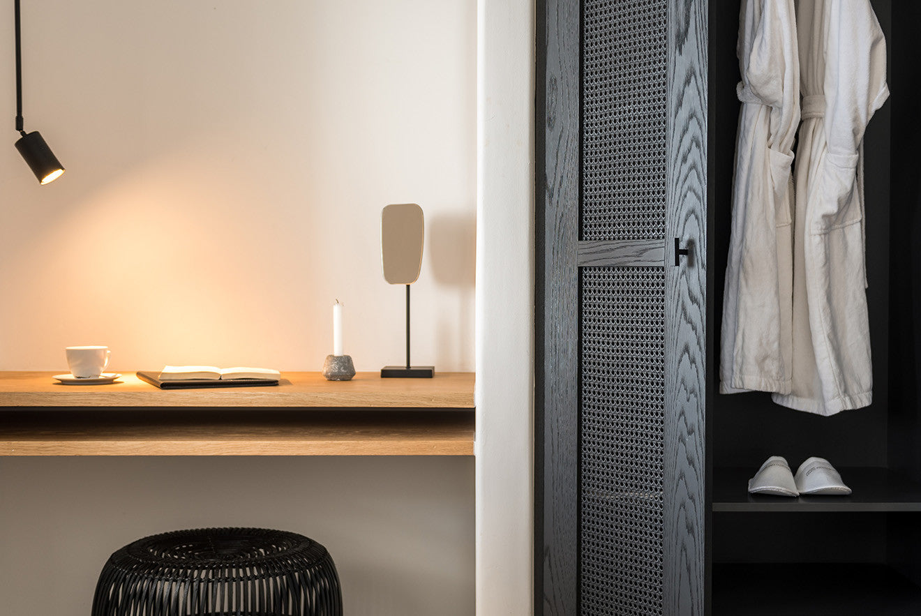 contrasting black doors on the wardrobes and storage against the white walls of the room