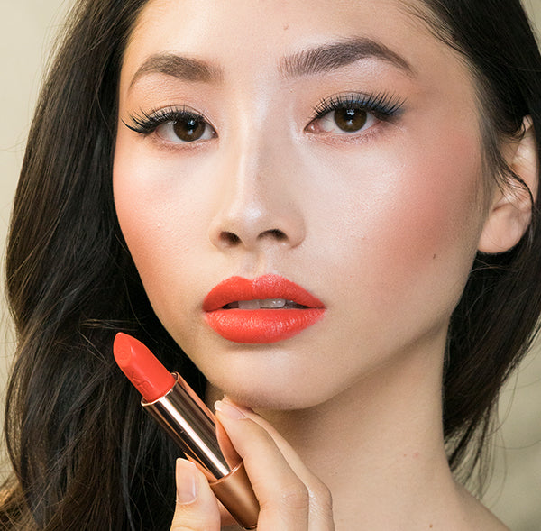 Model wearing Coral Dawn shade moisturising  natural lipstick