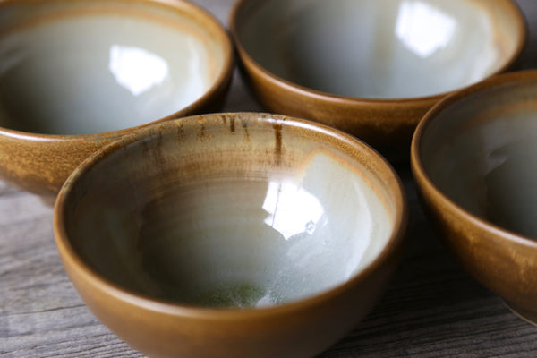 Four small bowls in golden earthy glaze