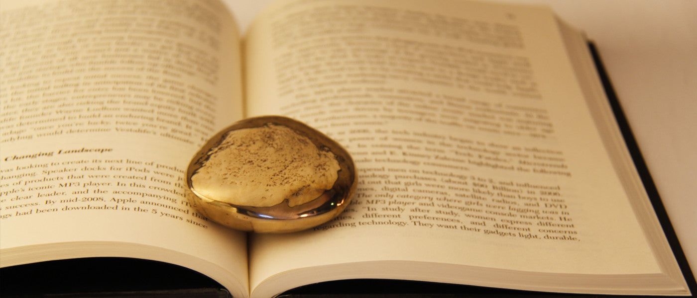 Pebble paperweight holding open a book