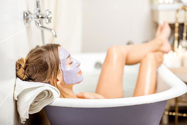 woman laying in bath with facemask