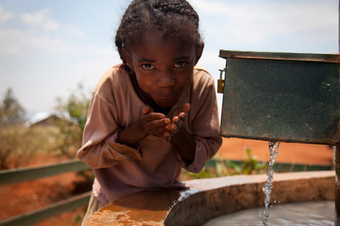 Merline, 9, getting clean water at the tapstand