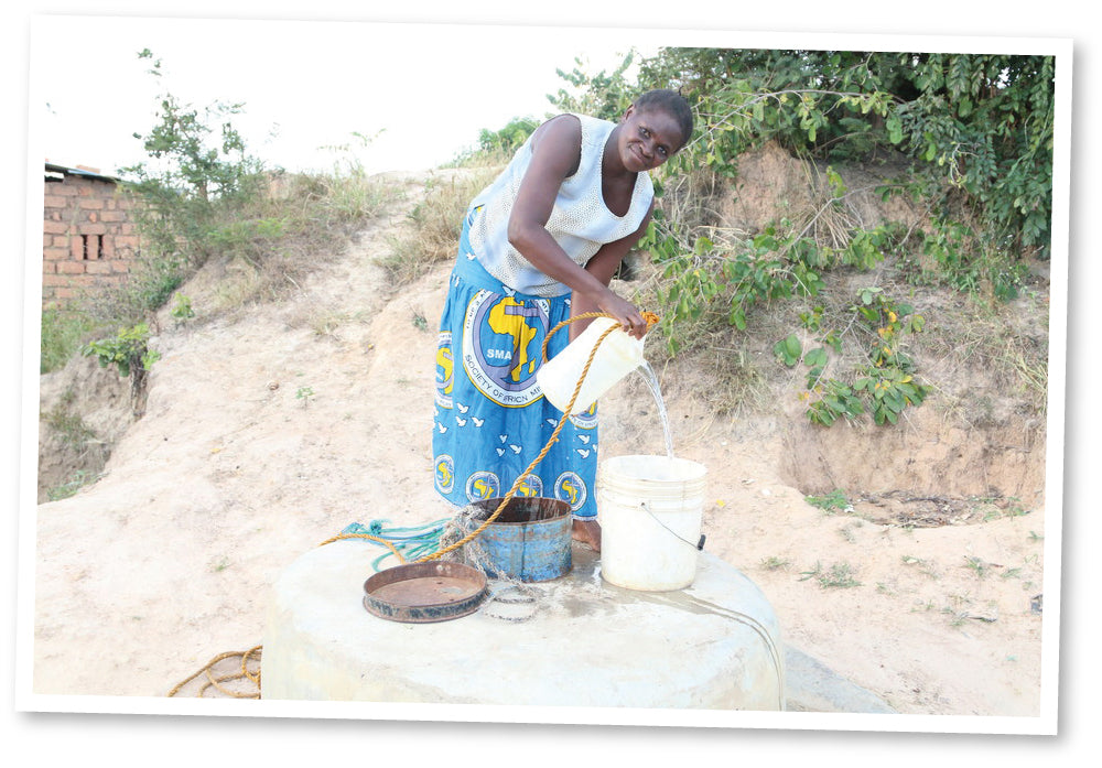 Petronella from Zambia using her community's well and rope pump