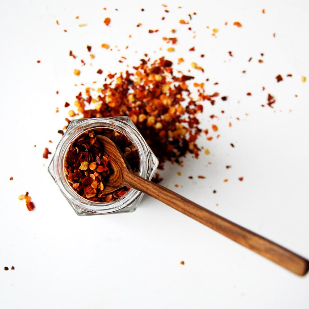 wooden spice spoon in a jar of chili flakes