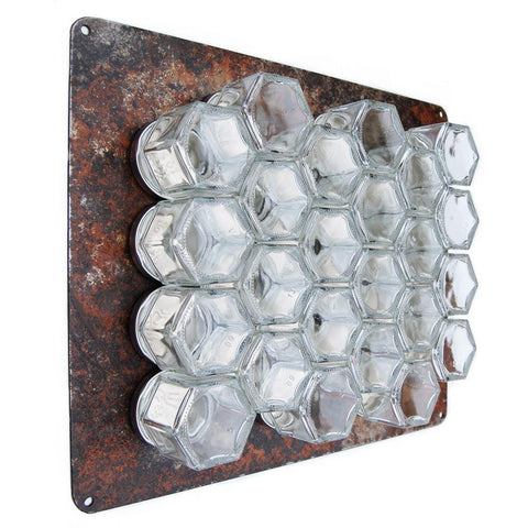 Rusted metal wall plate with magnetic spice rack stuck to it
