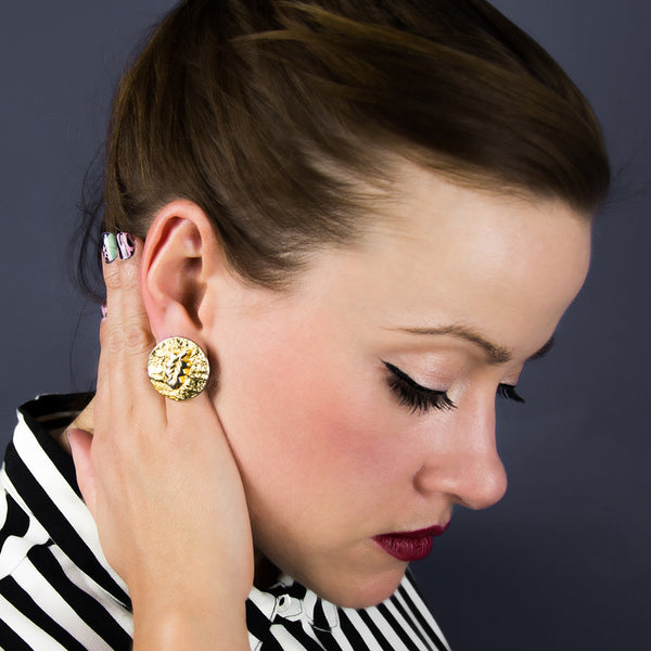 Woman wearing gold stud statement earring
