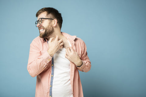 man scratching his itchy beard