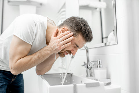 man washing his beard with water in a sink