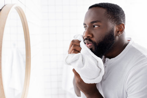 bearded man drying off his beard with a towel