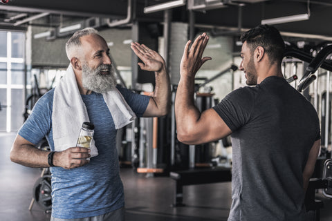 Older man with beard and young man with beard high fiving in a gym