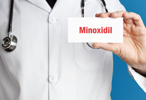 doctor holding sign that says minoxidil