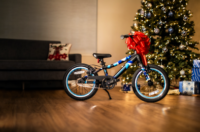"Guardian 16"" Ethos Bike in front of a Christmas tree with a large red bow"