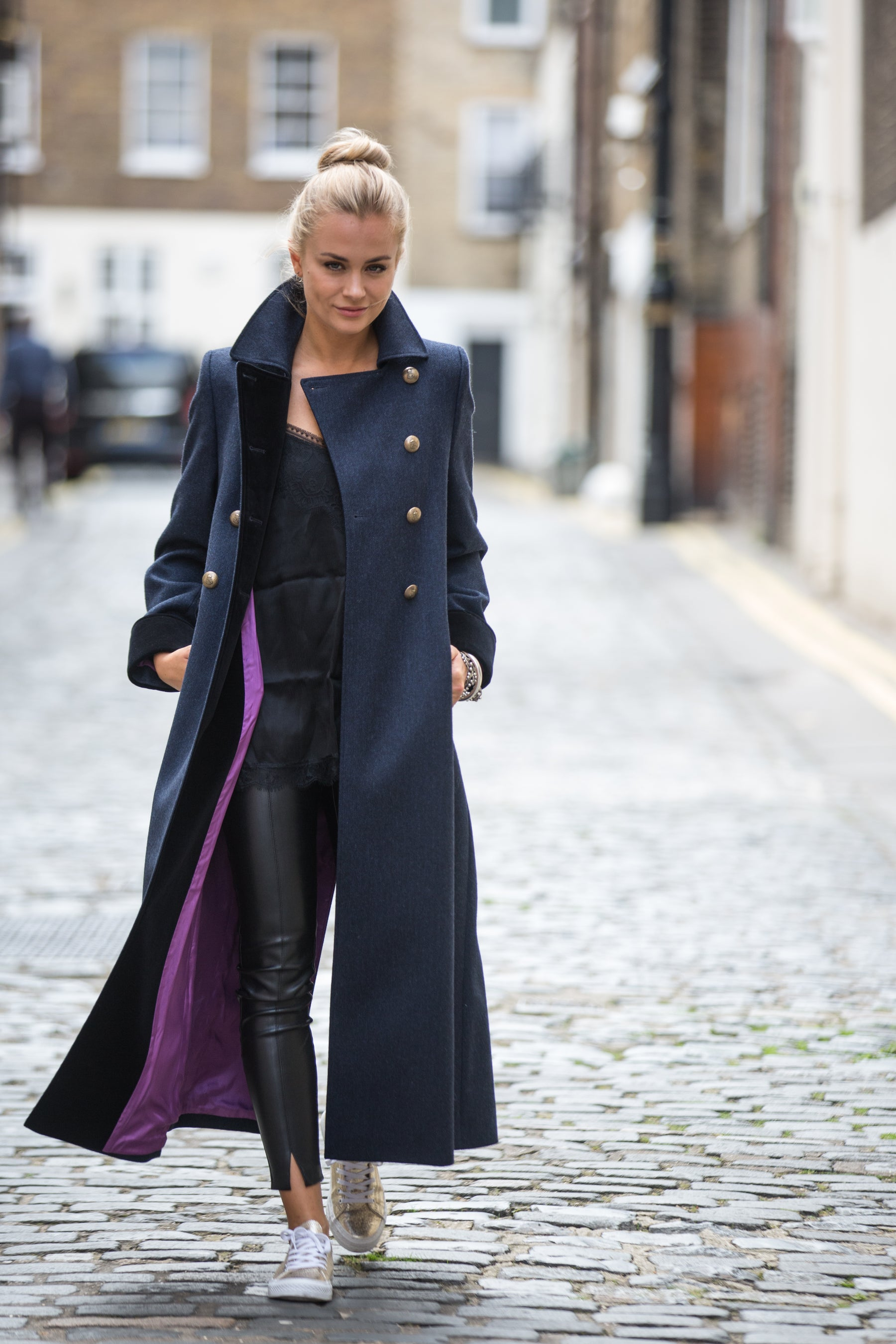 Girl wearing a long navy wool coat in an open and flowing style to reveal the coat's beautiful purple lining.  The pure wool coat has velvet details and military buttons. The coat is paired with leather jeans and gold trainers.
