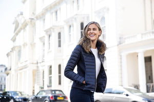 Girl wearing navy blue puffer jacket with stretch sides in London, styled with a white T shirt and jeans for a casual look.
