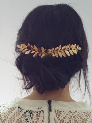 Woman wearing a long laurel leaf hair comb for a wedding