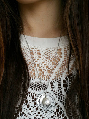 Woman wearing a personalized circle pendants with a round freshwater pearl necklace