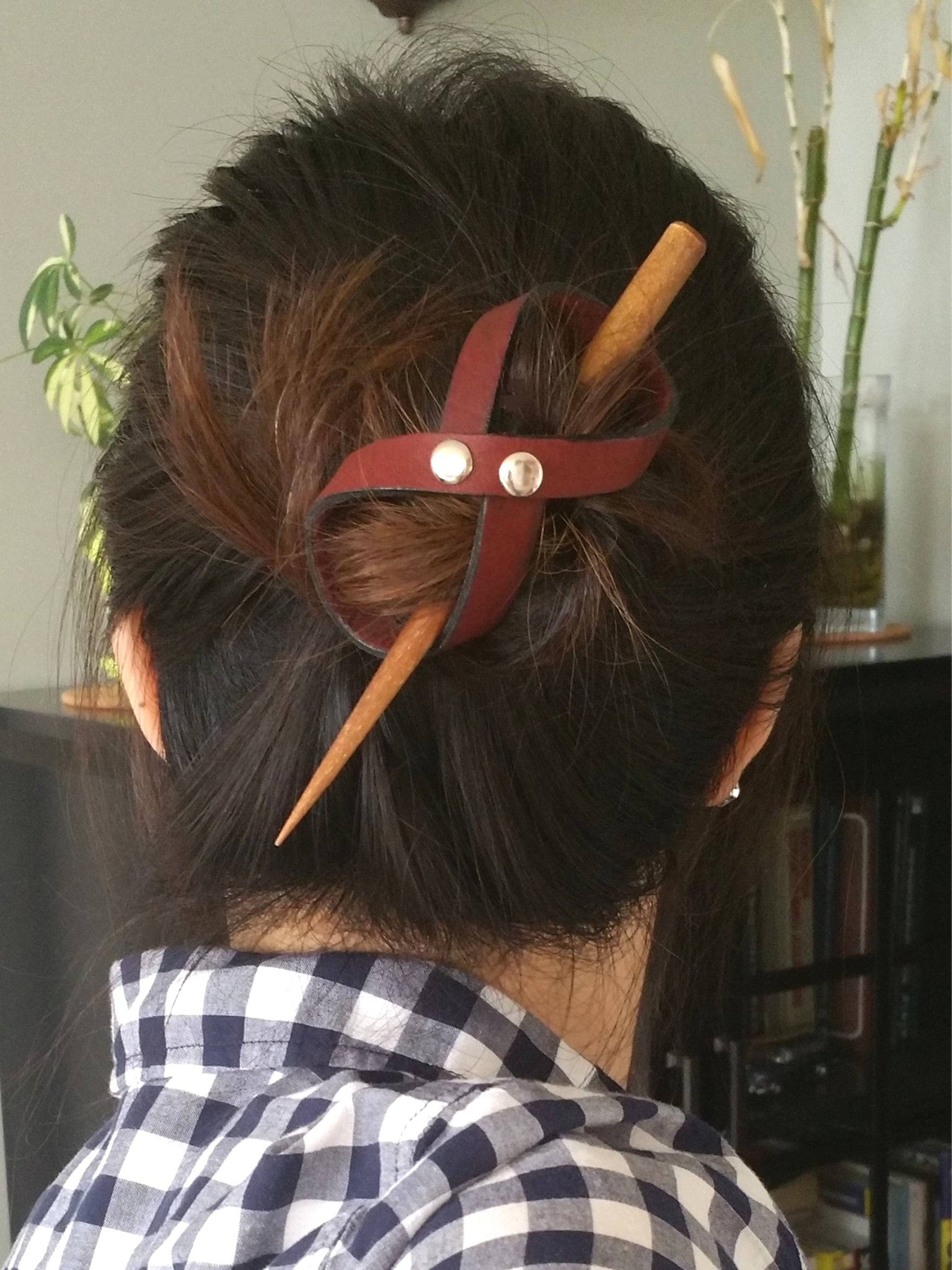 Woman wearing a leather hair bun holder with a hairstick