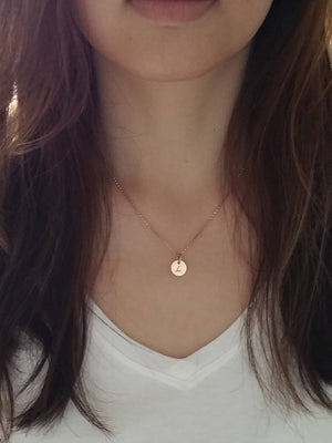 Woman wearing a personalized small rose gold circle with pearl charm necklace