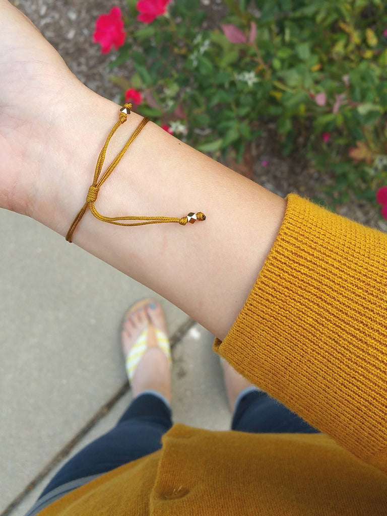 Model wearing a dainty rose gold personalized bracelet with mustard nylon cord