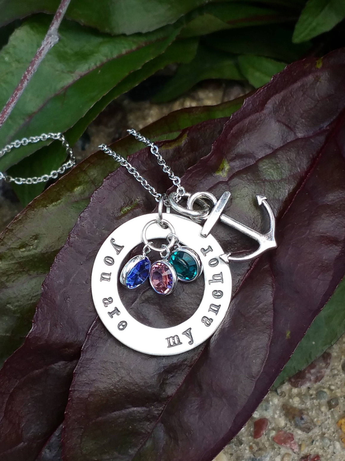 Personalized circle pendant with an anchor charm and birthstones in the middle necklace