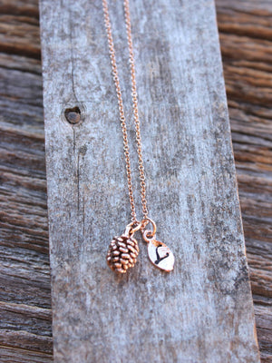 Dainty pine cone charm necklace in rose gold with an initial leaf