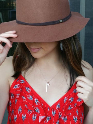 Model wearing a personalized rose gold vertical bar with initial leaves necklace