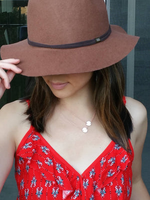 Model wearing a dainty rose gold slanted layered 2 discs necklace