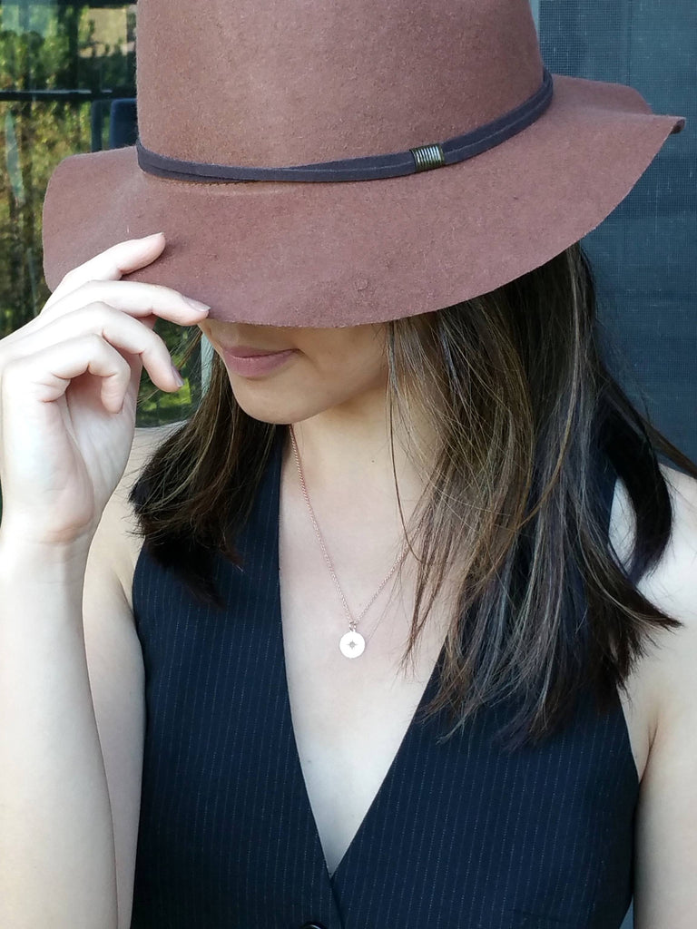 Model wearing a dainty compass charm necklace in rose gold
