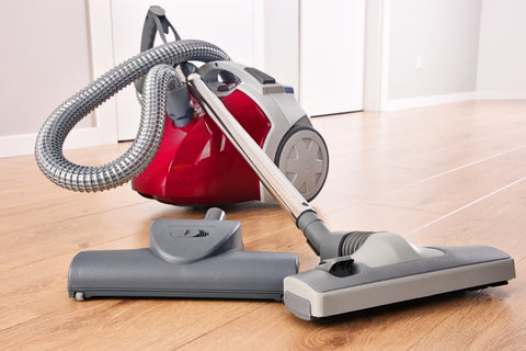 canister vacuum on hardwood floor